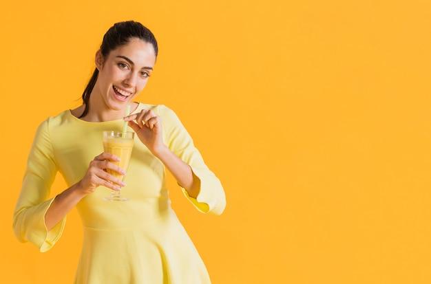Mujer feliz con un vaso de jugo