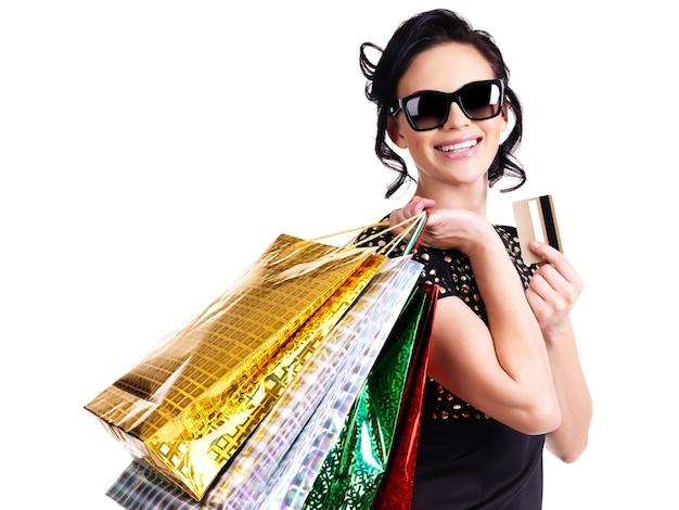 Mujer feliz en vasos con tarjeta de crédito y compras sobre fondo blanco.