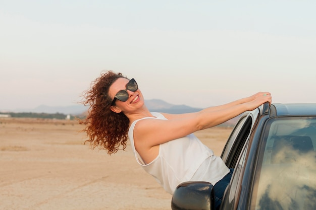 Mujer feliz en la ventanilla del automóvil