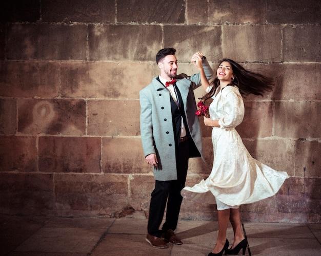 Mujer feliz en vestido bailando con el hombre en la calle