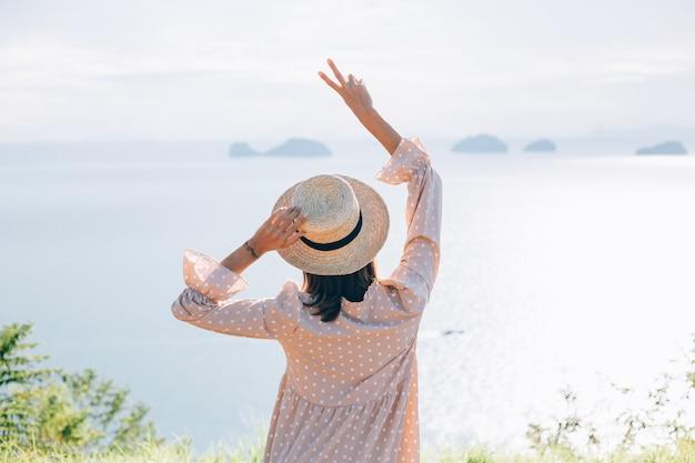 Mujer feliz en vestido lindo de verano y sombrero de paja de vacaciones con vistas exóticas tropicales