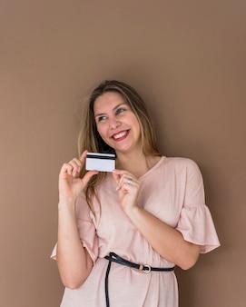 Mujer feliz en vestido de pie con tarjeta de crédito