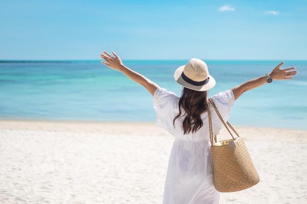 Mujer feliz viajera en vestido blanco y sombrero disfruta de hermosas vistas al mar