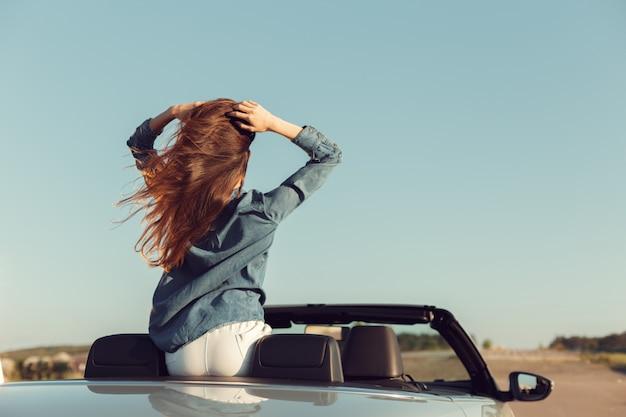 Mujer feliz viajero en auto descapotable