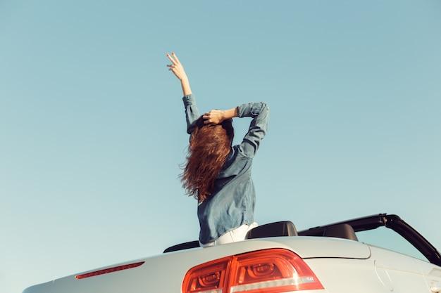 Mujer feliz viajero en coche descapotable