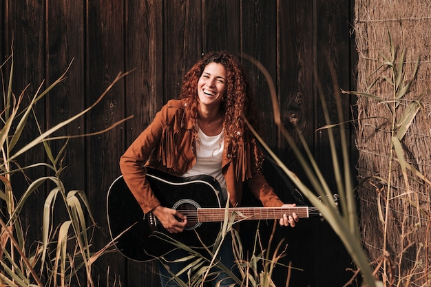Mujer feliz vista frontal tocando una guitarra