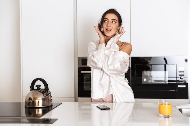 Mujer feliz vistiendo ropa de seda sonriendo, mientras está de pie en la cocina de casa