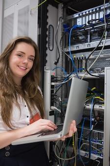 Mujer felizmente usando la computadora portátil para trabajar en servidores