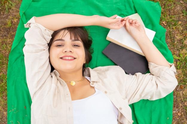 Mujer femenina alegre que miente en prado verde