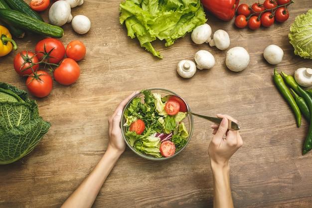 Mujer femenina manos sobre la mesa de la cocina de madera oscura con verduras, ingredientes de cocina, cuchara y herramientas, vista superior