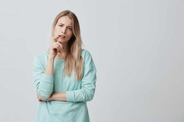 Mujer femenina rubia indignada que está insatisfecha con los resultados del examen o la competencia. mantiene el dedo sobre la boca abierta