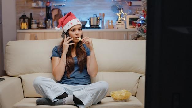 Mujer festiva hablando por teléfono inteligente con la familia