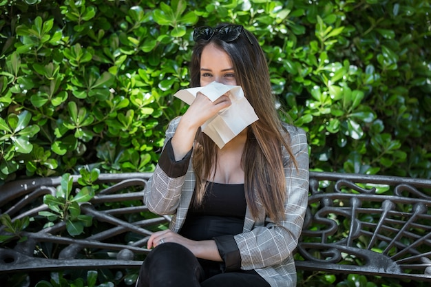 Mujer con fiebre del heno sonarse la nariz en el parque