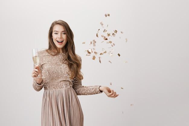Mujer de fiesta en traje de noche, bebe champán y lanza confeti