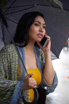 Mujer filipina con paraguas hablando por teléfono