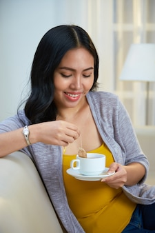 Mujer filipina que sumerge el bolso de té en taza