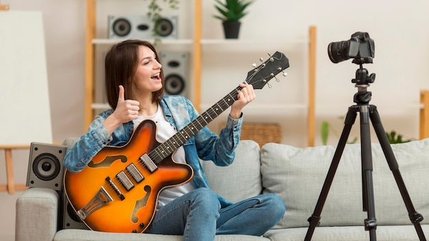 Mujer filmando video musical en casa