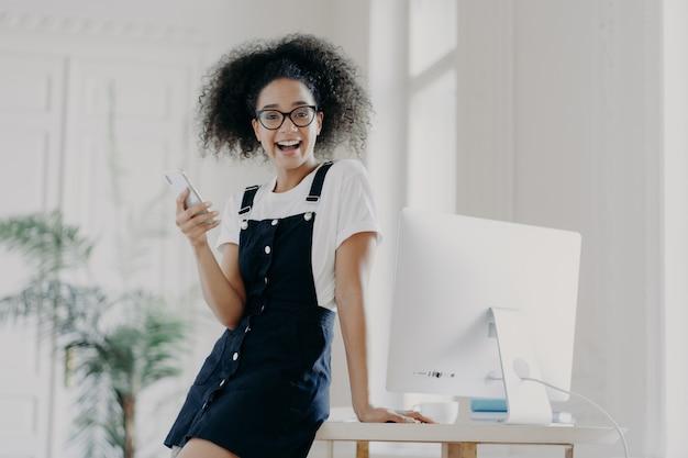La mujer financiera feliz y despreocupada usa el teléfono móvil, se alegra de recibir el salario a tiempo, posa cerca de la mesa de madera, usa la computadora para el trabajo, envía mensajes de texto y sonríe agradable