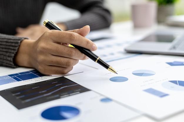 Una mujer de finanzas comerciales está revisando los documentos financieros de una empresa preparados por el departamento de finanzas para una reunión con socios comerciales. concepto de validación de la exactitud de las cifras financieras.