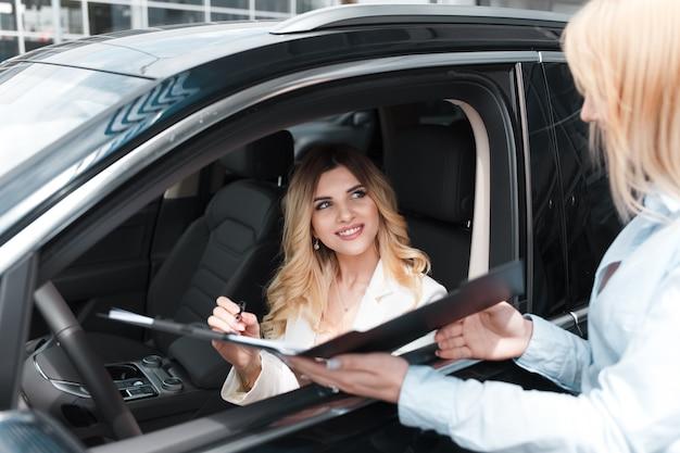 Mujer firma un acuerdo de concesionario de automóviles.
