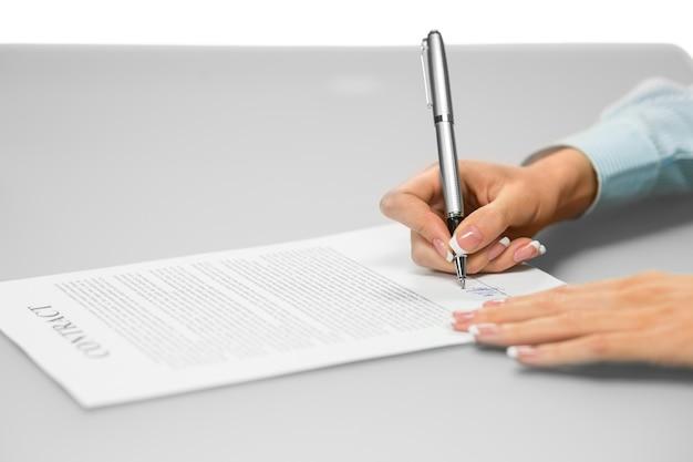 Mujer firma contrato comercial. solo queda una firma. una firma hace muchos cambios. piense antes de firmar.