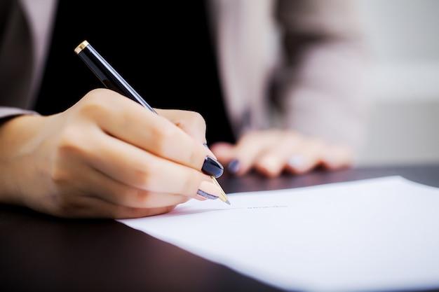 Mujer firma un contrato de compra de automóviles