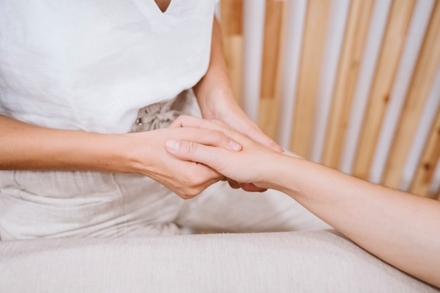 Mujer fisioterapeuta dando un masaje a un cliente en clínica