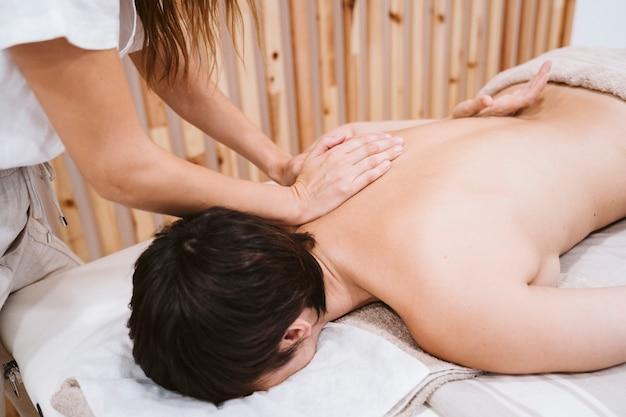 Mujer fisioterapeuta dando un masaje de espalda a un cliente en clínica