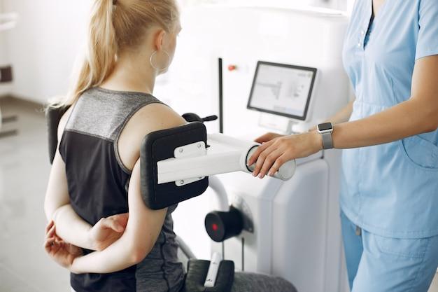 Mujer en fisioterapia haciendo ejercicios físicos con terapeuta calificado