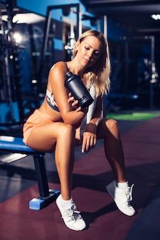 Mujer fitness con agitador posando en el gimnasio