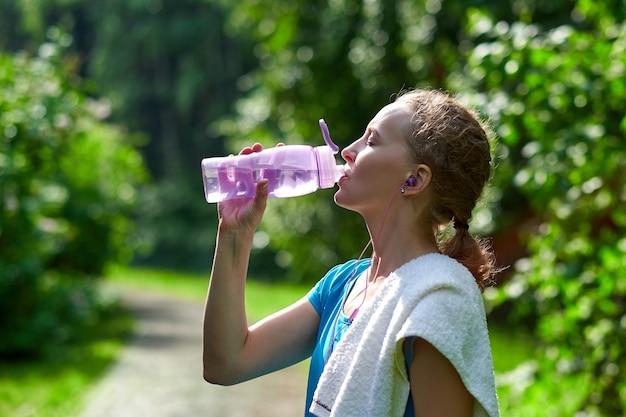Mujer fitness agua potable después de correr el entrenamiento en el parque de verano.