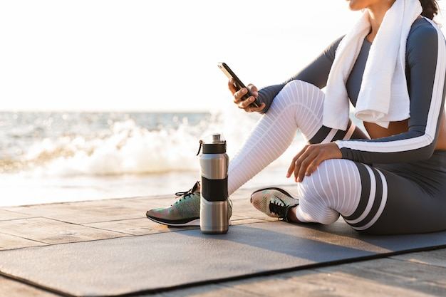 Mujer fitness al aire libre mediante teléfono móvil