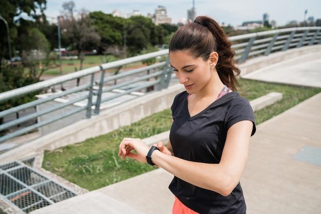 Mujer fitness control de tiempo en reloj inteligente.
