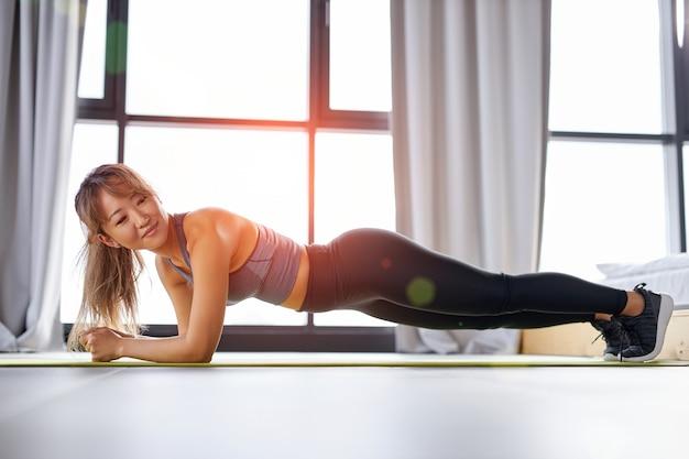 Mujer fitness coreana haciendo push up, hermosa mujer en ropa deportiva entrenamiento solo