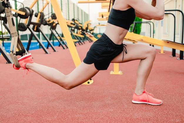 Mujer fitness deportivo haciendo entrenamiento trx al aire libre en el estadio