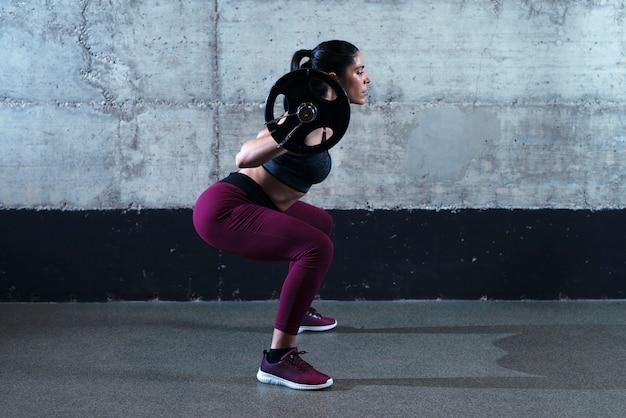 Mujer fitness deportivo en posición de cuclillas haciendo sentadillas y levantando pesas en el gimnasio