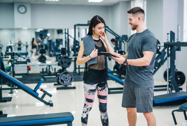 Mujer fitness ejercicio con entrenador físico en gimnasio.