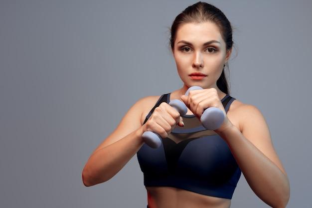 Mujer fitness ejercicio con pesas sobre fondo gris