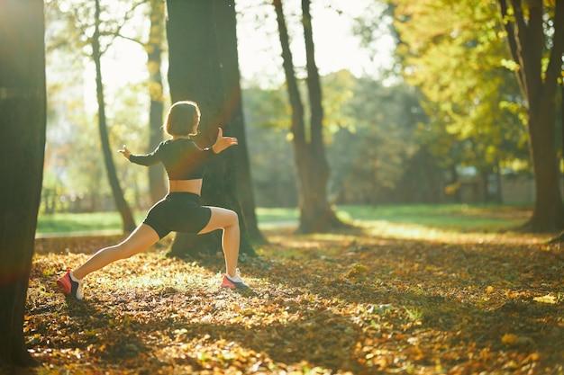 Mujer fitness estirando las piernas durante el día soleado en el parque