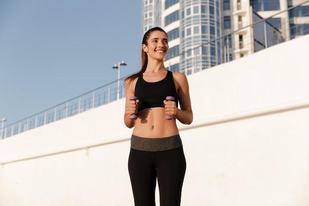 Mujer fitness feliz haciendo ejercicios con pesas mientras entrenaba en la mañana
