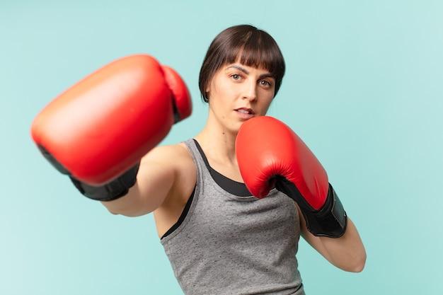 Mujer fitness con guantes de boxeo rojos.