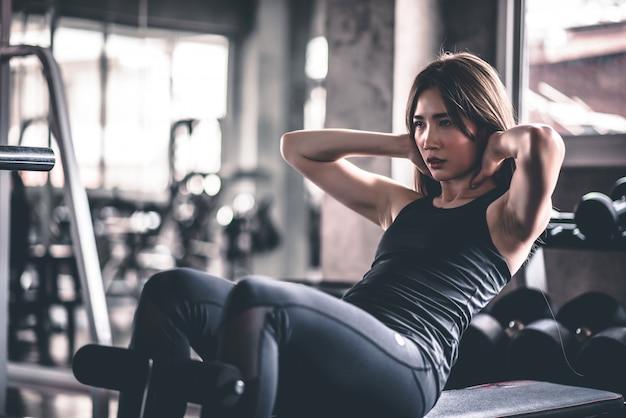 Mujer fitness haciendo abdominales haciendo ejercicio en el gimnasio.