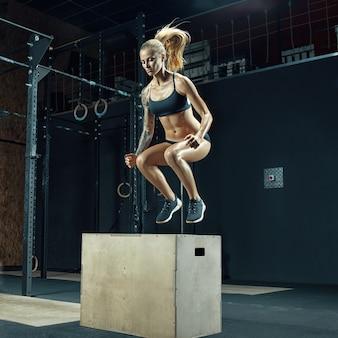 Mujer fitness haciendo ejercicio de salto de caja en el gimnasio ejercicio de salto de caja en el gimnasio moderno