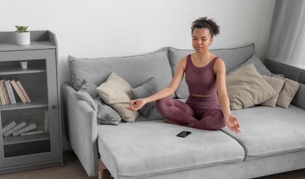 Mujer fitness haciendo yoga en casa Foto gratis