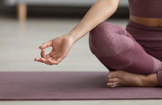 Mujer fitness haciendo yoga en una estera de yoga en casa