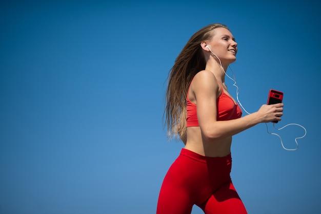 Mujer fitness joven corriendo en el cielo apaisada. el concepto de un estilo de vida saludable.