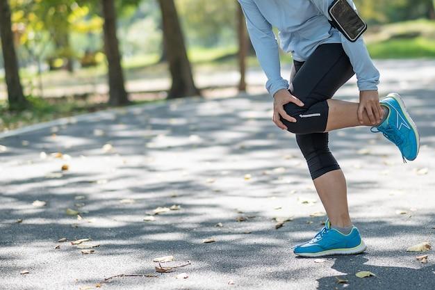Mujer fitness joven sosteniendo su lesión en las piernas de los deportes, dolor muscular durante el entrenamiento