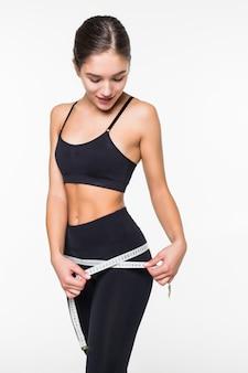 Mujer fitness medición de forma perfecta de hermosas caderas aisladas en pared blanca. concepto de estilos de vida saludables