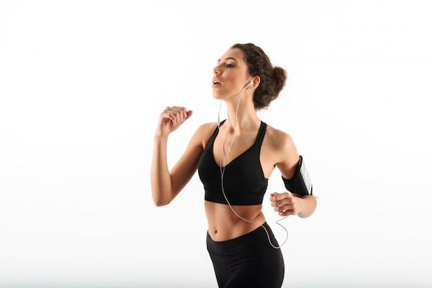 Mujer de fitness morena rizada concentrada corriendo y escuchando música