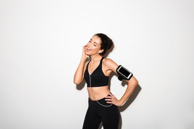 Mujer de fitness morena rizada contenta escuchando música por teléfono inteligente